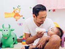 Να ενεργήσει Mom πατέρων γάλα σίτισης το ενός έτους βρέφος μωρών γιων του στην καρέκλα στοκ φωτογραφία
