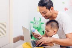 Να ενεργήσει Mom πατέρων γάλα σίτισης το ενός έτους βρέφος μωρών γιων του εργαζόμενων στο φορητό προσωπικό υπολογιστή στοκ φωτογραφίες