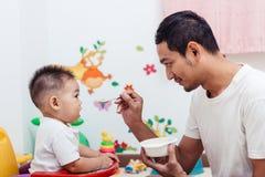Να ενεργήσει Mom πατέρων που ταΐζει το ενός έτους βρέφος μωρών γιων του στην καρέκλα στοκ φωτογραφίες με δικαίωμα ελεύθερης χρήσης
