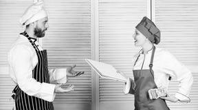 Να εξαργυρώσει επάνω Αρωγός μαγείρων που δίνει το μαγειρεύοντας φύλλο εργασίας στον αρχιμάγειρα Κύριο βιβλίο απολογισμού μαγείρων στοκ φωτογραφία με δικαίωμα ελεύθερης χρήσης