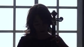 Να εξισώσει ενάντια στο κορίτσι παραθύρων παίζει το βιολοντσέλο κλείστε επάνω σκιαγραφία απόθεμα βίντεο