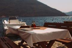 Να εξισώσει το ρομαντικό καθαρό πίνακα γευμάτων στον καφέ κόλπων Στοκ Φωτογραφίες