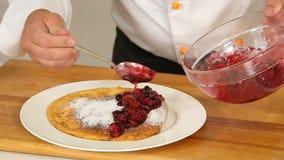 Να εξυπηρετήσει έψησε πρόσφατα την τηγανίτα με τη βανίλια sugarpowder και τη σάλτσα μούρων σε ένα άσπρο πιάτο απόθεμα βίντεο
