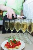 Να εξυπηρετήσει το πρόχειρο φαγητό κατά τη διάρκεια του γεγονότος CHAMPAGNE στα γυαλιά με ένα πρόχειρο φαγητό φρούτων Στοκ Εικόνες