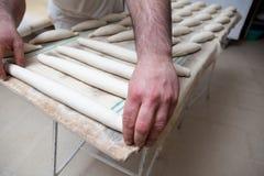 Να ζυμώσει και τοποθέτηση των κομματιών του ψωμιού πέρα από τον πίνακα ζύμωσης Στοκ εικόνα με δικαίωμα ελεύθερης χρήσης