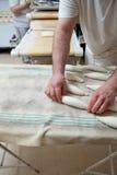 Να ζυμώσει και τοποθέτηση των κομματιών του ψωμιού πέρα από τον πίνακα ζύμωσης Στοκ Εικόνες