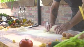 Να ζυμώσει μαγείρων ατόμων ζύμη για τα ιταλικά ζυμαρικά Μάγειρας αρχιμαγείρων που κάνει τη ζύμη για την πίτσα και την κοπή στο μα απόθεμα βίντεο