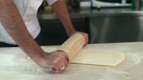 Να ζυμώσει Baker ζύμη με μια κυλώντας καρφίτσα στην κουζίνα του απόθεμα βίντεο