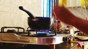 Να θερμάνει επάνω το τηγανίζοντας τηγάνι στη σόμπα Εγκαύματα πυρκαγιάς αερίου, απόθεμα βίντεο