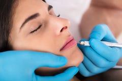 Να ισχύσει Cosmetologist μόνιμο αποτελεί στα χείλια Στοκ φωτογραφία με δικαίωμα ελεύθερης χρήσης
