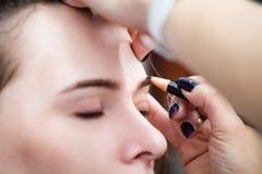 Να ισχύσει Cosmetologist μόνιμο αποτελεί (δερματοστιξία) στα φρύδια Στοκ Φωτογραφία