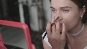 να κάνει αποτελεί Το κορίτσι με τα καλά μάτια που κοιτάζει στον καθρέφτη και το φρύδι βάφει το ειδικό μολύβι, 4k απόθεμα βίντεο