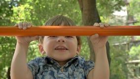 Να κάνει παιδάκι σηκώνει και ο νέος πατέρας του που βοηθά τον, που εκπαιδεύει στο πάρκο, καλοκαίρι απόθεμα βίντεο