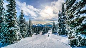 Να κάνει σκι κάτω από το ηλιοβασίλεμα σε ένα χειμερινό τοπίο υψηλό στον αλπικό στους λόφους σκι των αιχμών ήλιων Στοκ εικόνα με δικαίωμα ελεύθερης χρήσης