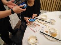 Να κάνει την πληρωμή σε ένα εστιατόριο μέσω των χρημάτων Wechat σε κινητό Στοκ Εικόνες