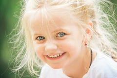 να κάνει το τρίχωμα Μικρό ευτυχές χαμόγελο παιδιών Τρίχα ένδυσης μικρών κοριτσιών στις κοτσίδες Μικρό κορίτσι με τα ξανθά μαλλιά  στοκ φωτογραφία