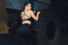 Ρόδα ροδών κτυπήματος γυναικών ικανότητας στη γυμναστική Κατάλληλος θηλυκός αθλητής που επιλύει με μια τεράστια ρόδα Πίσω άποψη Ν στοκ εικόνες με δικαίωμα ελεύθερης χρήσης