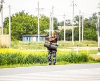 Να κάνει ωτοστόπ Αυτόματος-πώμα κοριτσιών Το κορίτσι με το σακίδιο πλάτης σταματά το αυτοκίνητο Ψηφοφορία για τη διαδρομή Στοκ Φωτογραφία