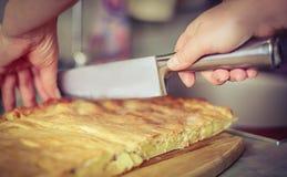 Να μαγειρεψει στο σπίτι την έννοια: ο τρύγος εξασθένισε την εικόνα woman's δίνει την κοπή μιας πίτας πατατών με το μαχαίρι chef στοκ εικόνες με δικαίωμα ελεύθερης χρήσης