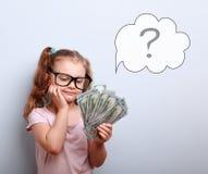 Να ονειρευτεί το χαριτωμένο κορίτσι παιδιών στα γυαλιά που κοιτάζει στα χρήματα και σκέψη στοκ φωτογραφίες