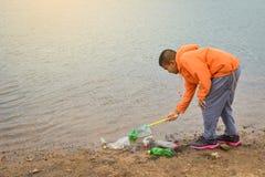 Να πάρει αγοριών κενό του πλαστικού μπουκαλιών Στοκ Εικόνες