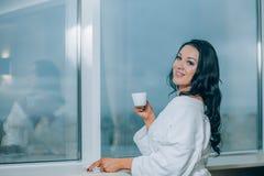 Να πάρει θερμός με το φρέσκο καφέ Όμορφη νέα γυναίκα στον άσπρο καφέ κατανάλωσης μπουρνουζιών και κοίταγμα μέσω ενός παραθύρου Στοκ εικόνες με δικαίωμα ελεύθερης χρήσης