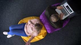 Να περιβάλει γύρω από το topshot του άνδρα που λειτουργεί με το lap-top και τη γυναίκα που μιλούν στο κινητό τηλέφωνο γυρίζει σε  απόθεμα βίντεο