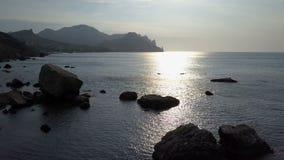 Να πετάξει προς τα πίσω πέρα από την επιφάνεια θάλασσας με τους βράχους και τις πέτρες στην ανατολή Βουνά, βράχοι, πέτρες στο wwa φιλμ μικρού μήκους