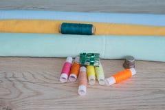 Να ράψει ακόμα τη ζωή: ζωηρόχρωμο ύφασμα το ψαλίδι και η ράβοντας εξάρτηση περιλαμβάνουν τα νήματα των διαφορετικών χρωμάτων, της Στοκ Εικόνα