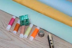 Να ράψει ακόμα τη ζωή: ζωηρόχρωμο ύφασμα το ψαλίδι και η ράβοντας εξάρτηση περιλαμβάνουν τα νήματα των διαφορετικών χρωμάτων, της Στοκ Φωτογραφία