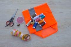 Να ράψει ακόμα τη ζωή: ζωηρόχρωμο ύφασμα το ψαλίδι και η ράβοντας εξάρτηση περιλαμβάνουν τα νήματα των διαφορετικών χρωμάτων, της Στοκ εικόνα με δικαίωμα ελεύθερης χρήσης