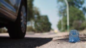 Να ρίξει μακριά το πλαστικό μπουκάλι από το παράθυρο αυτοκινήτων στο δρόμο απόθεμα βίντεο