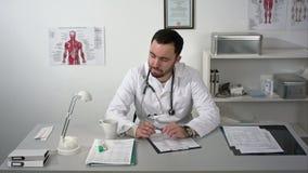 Να σκεφτεί έξω δυνατός Στοχαστικός νέος γενειοφόρος γιατρός στο ιατρικό γραφείο φιλμ μικρού μήκους
