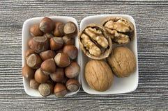 Να σταθεί δίπλα-δίπλα στο χωριστό πιάτο των ξεφλουδισμένων φουντουκιών και των ξεφλουδισμένων εικόνων ξύλων καρυδιάς Στοκ Εικόνες