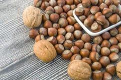 Να σταθεί δίπλα-δίπλα στο χωριστό πιάτο των ξεφλουδισμένων φουντουκιών και των ξεφλουδισμένων εικόνων ξύλων καρυδιάς Στοκ Εικόνα