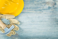 Να στηριχτεί τα καρφιά σφυριών νυχιών γαντιών ασφάλειας δέρματος κρανών στο ξύλο Στοκ Φωτογραφία