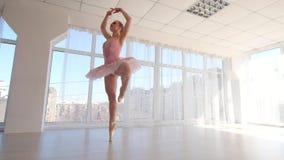 Να συναρπάσει το θηλυκό χορευτή μπαλέτου στο ρόδινο tutu που ασκεί και χαμόγελο απόθεμα βίντεο
