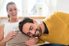 Να σύντομα--είστε μπαμπάς που ακούει στην κοιλιά της έγκυου συζύγου του Στοκ φωτογραφίες με δικαίωμα ελεύθερης χρήσης