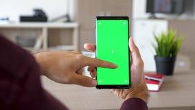 Να τυλίξει χεριών ατόμων κάτω σε ένα smartphone με την πράσινη χλεύη χρώματος οθόνης επάνω φιλμ μικρού μήκους