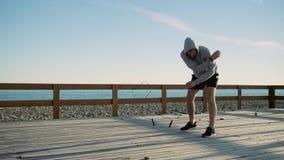 Να υπομείνει το άτομο πηδά κοντά στη θάλασσα, που περιστρέφει το σχοινί γύρω από τον φιλμ μικρού μήκους