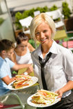 Να φέρει σερβιτορών στριμώχνει στα πιάτα το φρέσκο μεσημεριανό γεύμα Στοκ Φωτογραφία