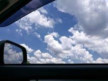 Να φανεί έξω το παράθυρο στο αυτοκίνητο με το μπλε ουρανό και το όμορφο υπόβαθρο σύννεφων στοκ εικόνες