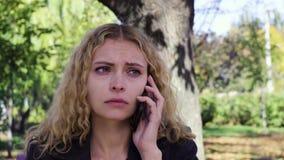 Να φωνάξει κοριτσιών που μιλά στην τηλεφωνική συνεδρίαση σε έναν πάγκο στο πάρκο απόθεμα βίντεο