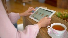 Να ψωνίσει on-line σε μια συσκευή ταμπλετών που κοιτάζει για να αγοράσει κάποια υποδήματα γυναικών ` s Διαφορετικές επιλογές ξεφυ απόθεμα βίντεο