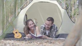 Νεαρή νέα γυναίκα άνδρων πορτρέτου αρκετά που βρίσκεται η μια κοντά στην άλλη στη σκηνή στη δασική ανάγνωση το βιβλίο Καυσόξυλο απόθεμα βίντεο