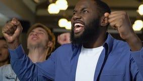 Νεαροί άνδρες που έχουν τη διασκέδαση στο φραγμό, προσέχοντας το ποδοσφαιρικό παιχνίδι, ενθαρρυντικό για τη νίκη απόθεμα βίντεο