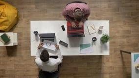 Νεαροί άνδρες που εργάζονται στο lap-top, που δίνει το έγγραφο στο συνάδελφο, topshot, που κάθεται στον πίνακα στο σύγχρονο γραφε απόθεμα βίντεο