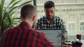 Νεαροί άνδρες που on-line να εργαστεί από τους φορητούς προσωπικούς υπολογιστές στον καφέ που κάνει την επιχείρηση απόθεμα βίντεο