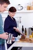 Νεαρός άνδρας και ευτυχής γυναίκα που προετοιμάζουν το πρόγευμα στην κουζίνα τους Στοκ φωτογραφία με δικαίωμα ελεύθερης χρήσης