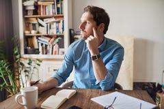 Νεαρός άνδρας βαθιά στη σκέψη εργαζόμενος από το σπίτι Στοκ Φωτογραφία